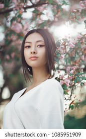 Gorgeous asian woman with perfect skin creartive art make-up wearing trendy white japanese kimono standing agaist flower background in the garden. Close-up fashion portrait outdoors. Spring blossom of
