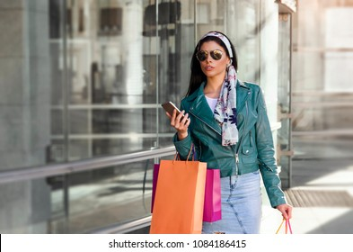Gorgeous, attractive city girl walking  with shopping bags while holding smartphone in her hands