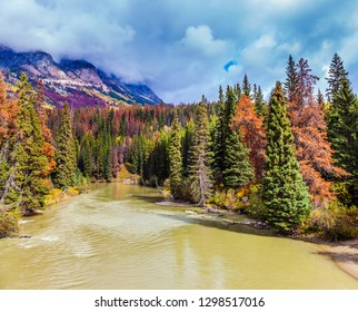 Gorgeous autumn in the Rockies of Canada. Lush clouds are flying across the sky. The picturesque river among the mountains and colorful forests. The concept of active, eco-and photo-tourism