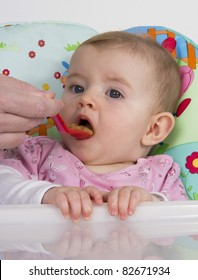 Gorgeous baby girl sitting in highchair being fed with pureed food