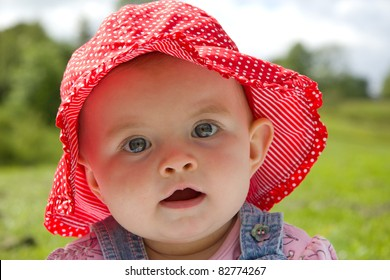 Gorgeous baby girl sitting in a park wearing a cute summer hat