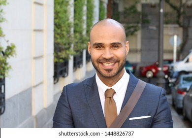 Gorgeous bald businessman smiling on the street