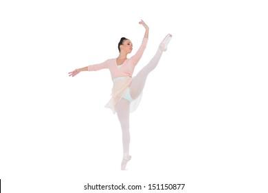 Gorgeous ballerina dancing rising her leg on white background