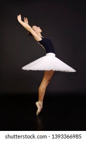 Gorgeous ballerina in a white tutu dancing ballet. Studio shooting on a dark background , isolated images.