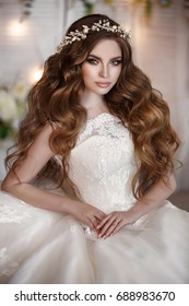 Gorgeous Beautiful Bride portrait with wedding makeup and long curly hair wears cristal wreath and bridal lace dress. Fashion model in elegant marriage dress posing at flowers interior in studio.