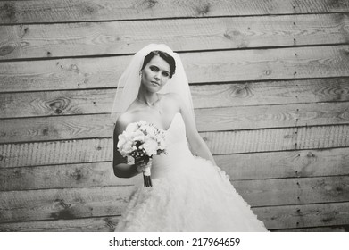 Gorgeous beautiful brunette  bride in white dress with bouquet.