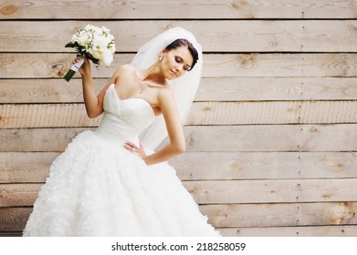 Gorgeous beautiful brunette  bride in white dress with bouquet on wood background.