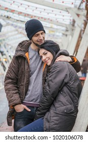 Gorgeous beautiful caucasian woman with a man on a walk in european city at winter. Couple wear casual grey outfit and hugging each other. Cold weather, christmas lights on a background