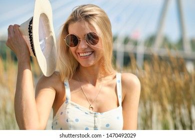 gorgeous beautiful woman in long white  dress and  hat walking.  Portrait of happy girl in the morning outdoors