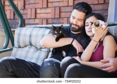 Gorgeous beautiful young couple holding cats in hands. Relax and love. Animal care. Animal lovers