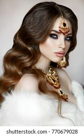 Gorgeous Beauty Indian Woman with wedding jewelry and furs. Fashion arab model with blue eyes wear golden jewelry and posing with veil and white furs luxury portrait. Rich indian Bride