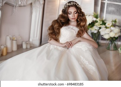 Gorgeous beauty young bride portrait. Beautiful bride with wedding makeup and jewelry wreath on long curly hair. Bridal fashion model with blue eyes posing in interior.