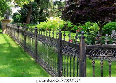 Gorgeous black wrought iron fencing marking the property lines of home and gardens.