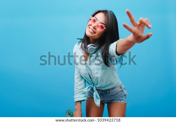 Gorgeous black-haired female model in vintage outfit posing with peace sign on blue background. Catching asian lady in sunglasses spending time on photoshoot and cute smiling.
