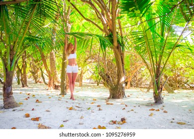 Gorgeous blond young woman with white hotpant and top clings to palm leaf