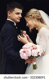 Gorgeous blonde bride putting on boutonniere on handsome groom in suit