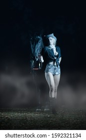 Gorgeous blonde cowboy girl in denim shorts wearing hat and standing next to black horse