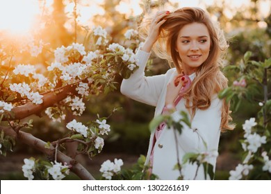 gorgeous blonde girl in blossoming garden. Girl near tree not look into camera. Girl in spring  garden. Spring concept. Beautiful girl in orchard