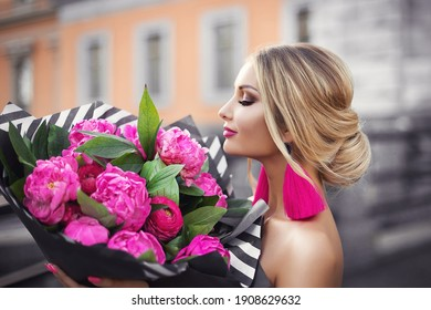 A gorgeous blonde girl in a couture fashion dress with pink peonies and black and white stripes with a bouquet of bright pink flowers.