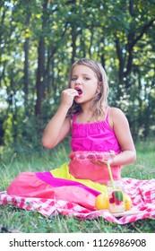 Gorgeous blonde girl having a picnic outdoors eating raspberries and drinking lemonade
