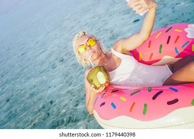 Gorgeous blonde girl in white bikini doing selfie in her doughnut floaty