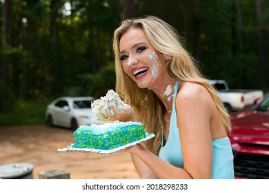 A gorgeous blonde model enjoys eating her birthday cake at a local picnic