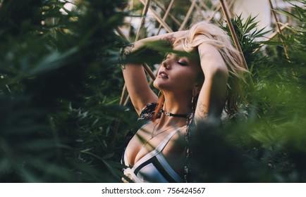 Gorgeous blonde relaxing in a cannabis garden