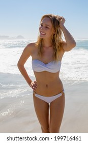 Gorgeous blonde in white bikini standing by the sea on a sunny day