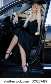 Gorgeous blonde woman in evening dress drives luxury cars