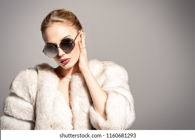 Gorgeous blonde woman posing in luxurious fur coat and sunglasses. Fashion, beauty. Studio shot.