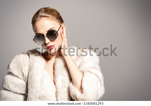 Gorgeous blonde woman posing in luxurious fur coat and sunglasses. Fashion, beauty. Studio shot.
