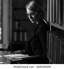 Gorgeous blonde woman wearing black tweed suit and glasses standing beside bookcase and reading book. Young seductive female model dressed in skirt and jacket at library. Smart is new sexy concept.