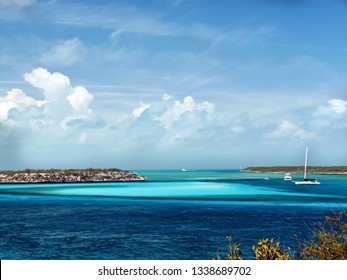 gorgeous blue water surrounds a tropical island with a sailboat