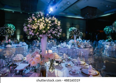 Gorgeous bouquets of white roses stand on the dinner tables