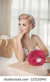 Gorgeous bride blonde in wedding dress in luxury interior with diamond jewelry posing at home and waiting for groom. Romantic rich happy girl in bridal dress smiling have final preparation for wedding