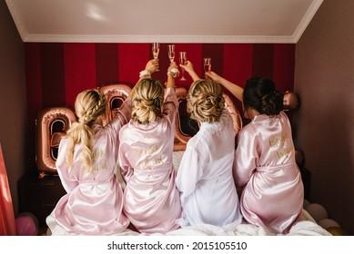 Herrliche Brautjungfern und Brautjungfern toast mit Wein und amüsieren sich am Hochzeitstag. Mädchen, die eine Brille mit Getränken halten und sich auf einem Hintergrund von Ballons halten. Rückansicht.
