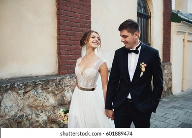 Gorgeous bride in elegant dress admires handsome groom walking with him along stone street