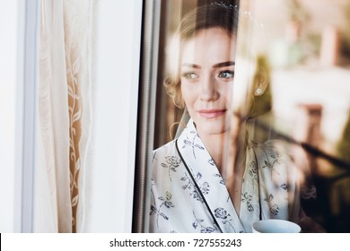 Gorgeous bride in elegant robe drinking coffee in luxury hotel room face closeup of dreamy expression, morning before the wedding preparation, window reflection