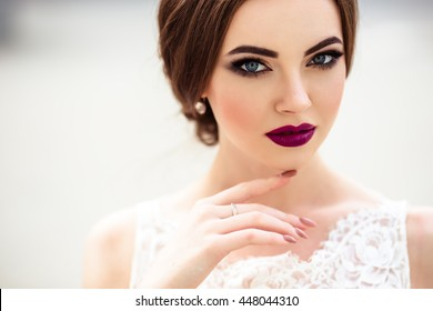 prächtige Braut mit Modebezug und Frisur in einem luxuriösen Hochzeitskleid