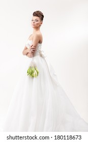 gorgeous bride in long white luxury dress posing in the studio