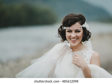 Gorgeous bride with short brunette hair smiles while posing by the river