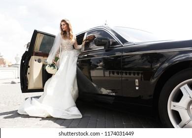 Gorgeous bride steps out of a rich black car