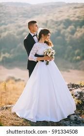 gorgeous bride and stylish groom hugging, boho wedding couple, luxury ceremony at mountains with amazing view,