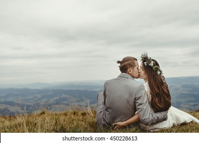 gorgeous bride and stylish groom kissing on top,  boho wedding couple, luxury ceremony at mountains with amazing view, space for text