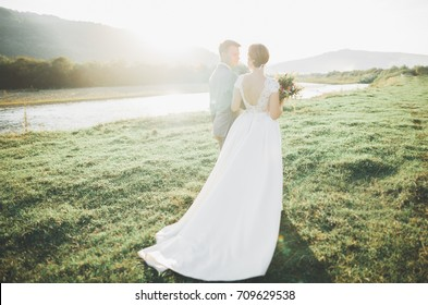Gorgeous bride and stylish groom walking at sunny landscape, wedding couple, luxury ceremony mountains with amazing view, space for text