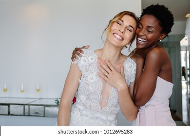 Gorgeous bride in wedding gown having fun with bridesmaid in hotel room. Cheerful bride and bridesmaid on the wedding day.