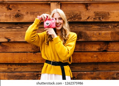 Gorgeous, bright blonde with curls makes  photo on her pink insta camera. Photo of a girl on wooden background in knitted sweater