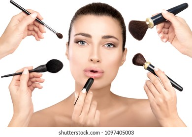 Gorgeous brunette beauty model in makeup process. Beauty concept with cosmetics brushes in the hands of beauticians applying make up to the face of a beautiful girl. Closeup isolated on white.