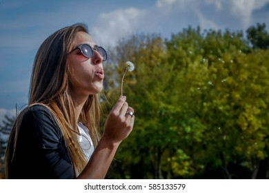A gorgeous brunette blowing a dandelion on a warm spring day in Serbia