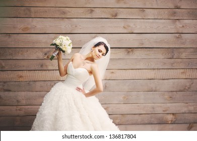 Gorgeous  Brunette bride with bouquet outdoor, posing